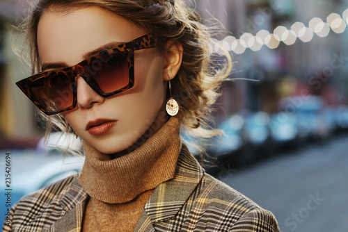 Outdoor close up fashion portrait of young beautiful fashionable girl wearing stylish animal, leopard print sunglasses, turtleneck, posing in street of european city. Copy, empty space for text