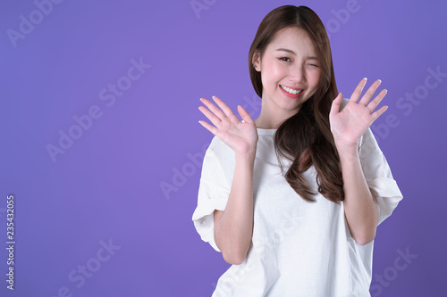 Fotografie, Obraz  Asian woman glad and hand up, white t-shirt clothing, purple background