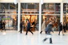Shopper Walking In Front Of Shop Window At Dusk