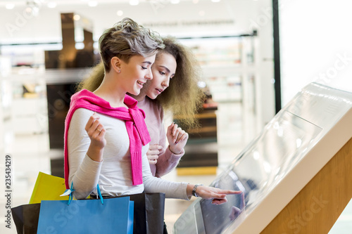 Photo Two adult caucasian girlfriends use information kiosk at shopping center