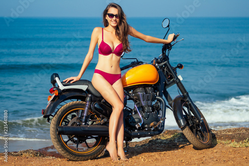 Sexy girl in a red bikini swimsuit sitting on a motorcycle royal