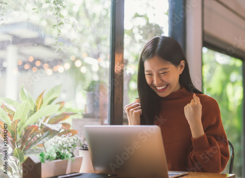 Fototapety, obrazy: Young Asian woman celebrate success or happy pose with laptop