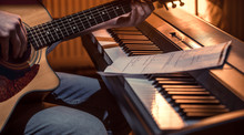 Man Playing Acoustic Guitar And Piano Close-up, Recording Notes