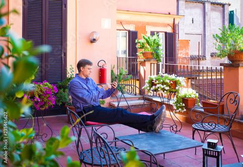 Fotografie, Obraz  Caucasian man  sitting on Italian veranda looking at cellphone