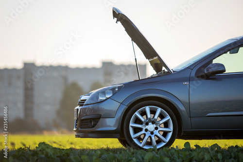 Fotografía Side view detail of car with open hood on empty gravel field road on blurred apartment building and clear bright sky copy space background
