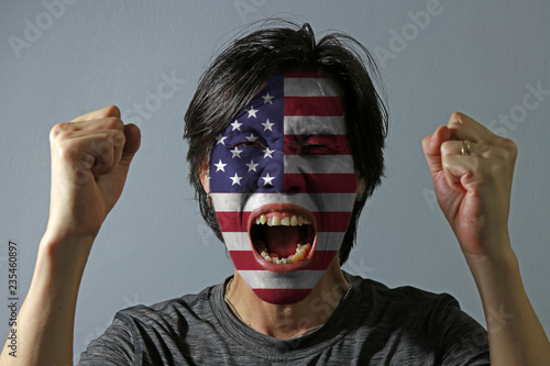 Fotografía  Cheerful portrait of a man with the flag of United States of America painted on his face on grey background