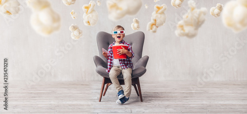 Surprised kid with popcorn in 3d glasses