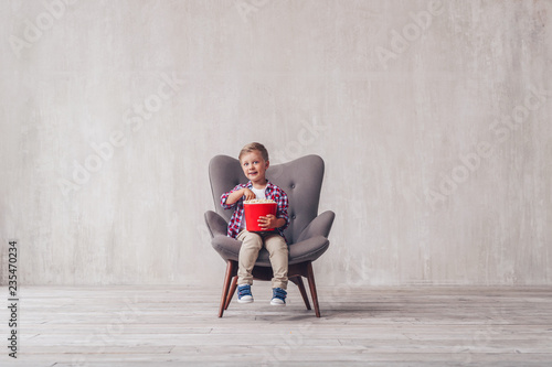 Smiling little spectator with popcorn