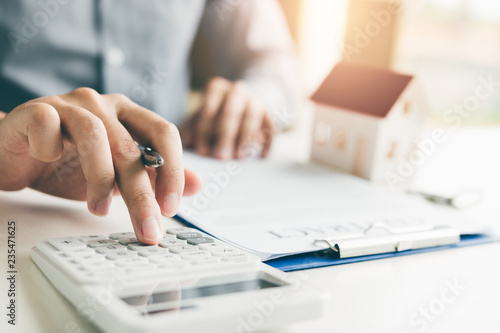 Fotomural  Home agents are using a calculator to calculate the loan period each month for the customer