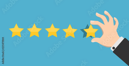 Fotografía  Hand putting five gold stars on blue background
