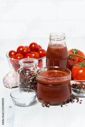 Fotobehang Kruiderij Products made with fresh tomato - sauce, juice and seasonings on white table, vertical