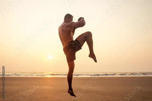 Fotografía Strong boxer shirtless coach during kickboxing exercise with trainer in boxing gloves at sunset