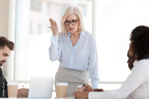 Photo Angry powerful mature businesswoman boss scolding employees frustrated by bad wo