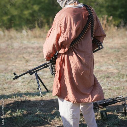 Fototapeta Machine gun in the hands of a soldier in red traditional muslim dress