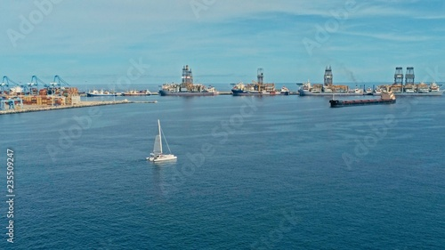 Tuinposter Canarische Eilanden aerial drone image of the harbor with cargo container oil tanker ships and a sailboat at the approach area