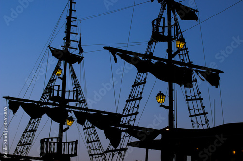 Keuken foto achterwand Schip romantic and atmospheric sea shot of vintage old pirate medieval ship silhouette shapes of mast and sails with small lamps with yellow illumination on evening twilight blue sky background