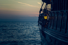 Yellow Illumination From Soft Focus Vintage Lamp In Over Board Of Wooden Old Pirate Ship On Sea Surface Landscape With Horizon Line In Evening Dark Twilight Time