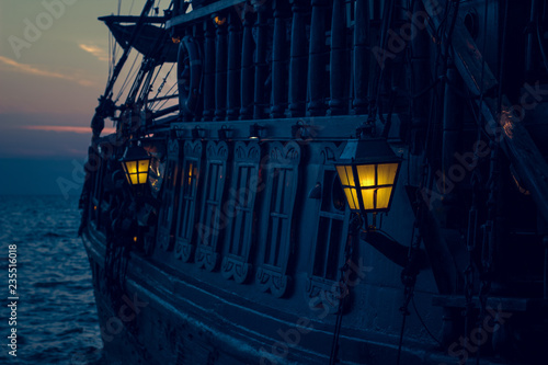 Foto auf Leinwand Schiff yellow illumination from soft focus vintage lamp in over board of wooden old pirate ship on sea surface landscape with horizon line in evening dark twilight time