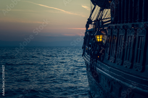Photo Stands Ship yellow illumination from soft focus vintage lamp in over board of wooden old pirate ship on sea surface landscape with horizon line in evening dark twilight time