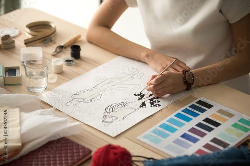 Fotografie, Tablou Female clothing designer coloring sketch, drawing with brush at workplace close