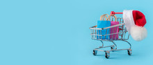 Online Shopping, Christmas Discounts Packaging Cardboard Boxes, Packages, Santa Hat, In A Cart On A Blue Background Banner