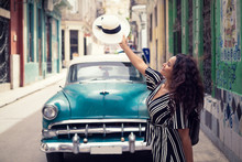 Young Beautiful Black Woman With A Typical Cuban Hat Standing In The Old Streets Of Havana Cuba In Front Of A Classic Car Holding The Hat Right Over The Car.