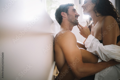 Fototapeta Young couple being intimate in bedroom. Sensual lovers making love in bedroom. obraz