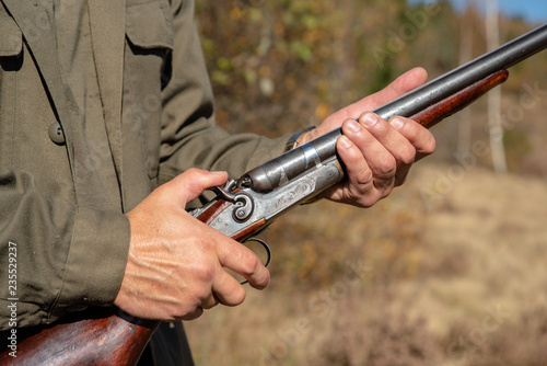 Hunter with horizontal double-barreled shotgun, pull the trigger,