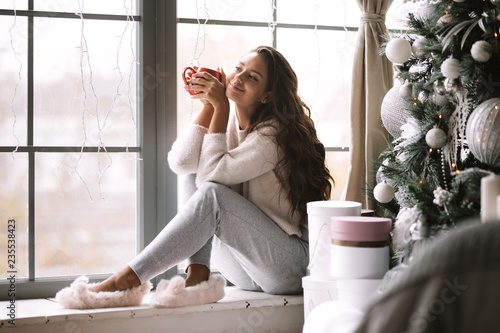 Fotografía Nice dark-haired girl dressed in pants, sweater and warm slippers holds a red cu