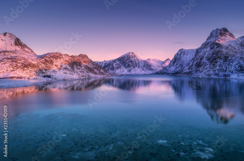 Foto op Canvas Candy roze Aerial view of snow covered mountains and colorful sky reflected in water at dusk. Winter landscape with sea, snowy rocks, purple sky, reflection at sunset. Lofoten islands, Norway at twilight. Nature