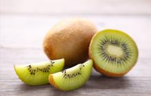 Fresh Kiwi Fruit And Slices Of Kiwi On Grey Wooden Background