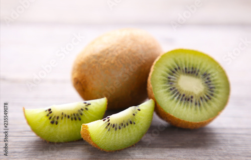 Fresh kiwi fruit and slices of kiwi on grey wooden background