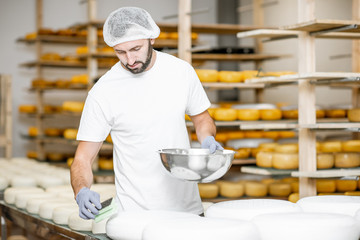 Obraz na PlexiMan rubing cheese wheels with wax at the cheese manufacturing with shelves full of cheese on the background