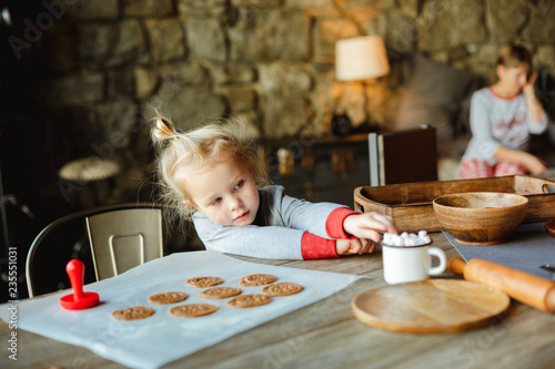 Fotografía  A charming little girl reaches for marshmallows in a Cup of cocoa, which stands