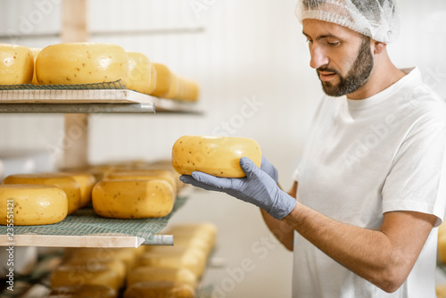 Obraz na plátně Man checking the quality of the fresh cheese wheels after the waxing and salting