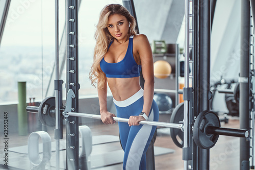Sexy girl wearing sportswear is posing next smith machine in the fitness center.