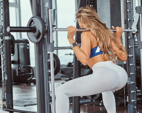 Fotografia Beautiful fitness girl doing squats on smith machine at the gym.