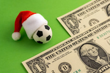 Christmas Sports Betting. Red Santa Claus Hat Is Dressed On A Souvenir Soccer Ball. Two Bills Of One Dollar On A Green Background. The Concept Of New Year's Football Victory Or Loss.