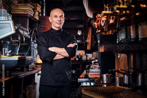 Fototapeta Confident chef posing with his arms crossed and looking at a camera in restaurant kitchen. obraz