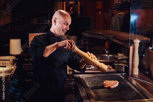 Fotografía  Master chef cooking delicious beef steak on a kitchen in a restaurant, pepper the meat with a pepper mill