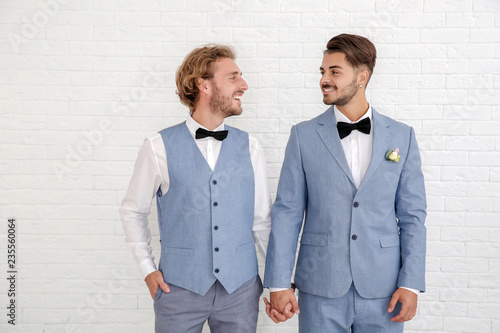 Happy newlywed gay couple in suits against white wall