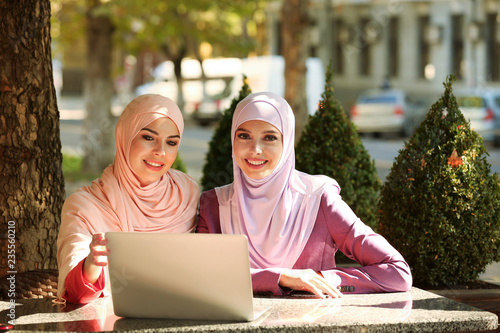 Muslim women with laptop sitting in outdoor cafe