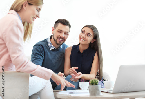 Female real estate agent working with couple in office Canvas Print