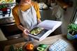 Leinwandbild Motiv Happy woman reading a cookbook in the kitchen