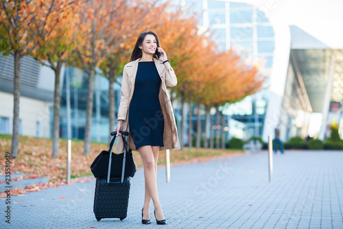 Girl carrying suitcase by streets Wallpaper Mural