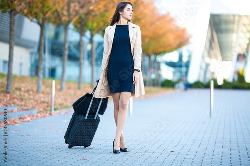 Girl carrying suitcase by streets Canvas Print