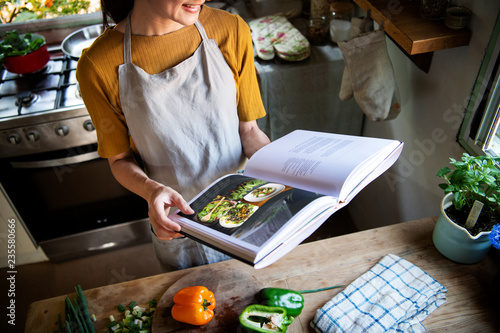 Fototapeta Happy woman reading a cookbook in the kitchen obraz