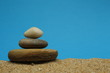 A cairn or Zen pile of pebbles on sea sand.