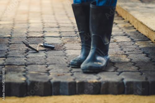 Fototapeta School janitor builds a brick pathway in school, Selective focus obraz na płótnie
