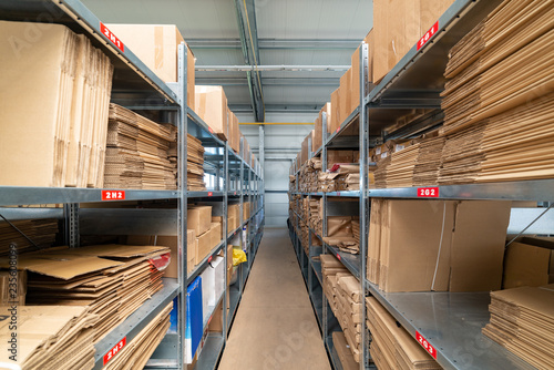 Poster Bibliotheque Warehouse shelves with cardboard boxes and packs in paper packaging